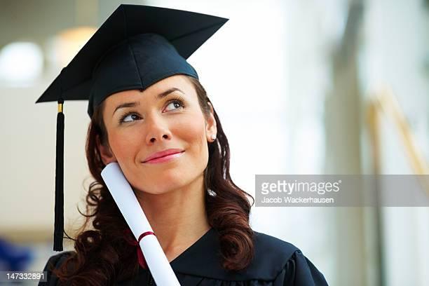 Junge Frau in Graduierung mit Diplom