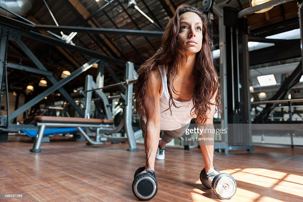 Young woman at gym doing pushups on dumbbells : Stock Photo