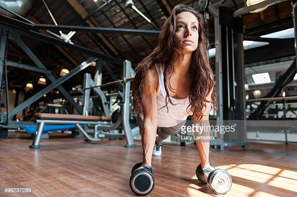 young woman at gym doing pushups on dumbbells - lucy lambriex stockfoto's en -beelden