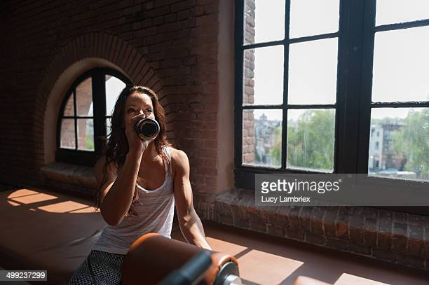 Young woman at gym taking a break, drinking water