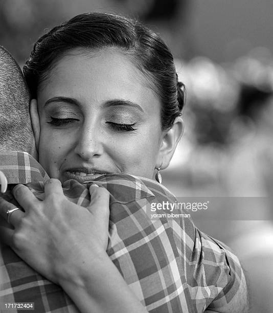 Young woman, at her twenties, hugging am man , while smiling and closing her eyes. B&W portrait.