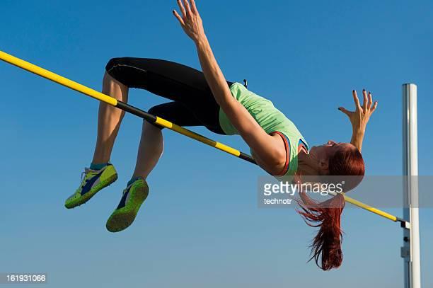 Jeune femme au saut en hauteur