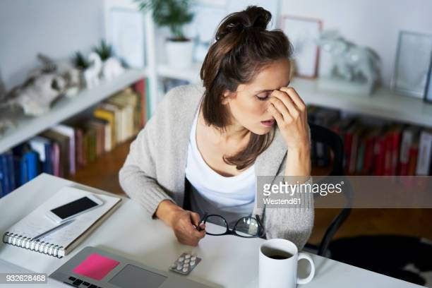 young woman at home at desk suffering headache - krankheit stock-fotos und bilder