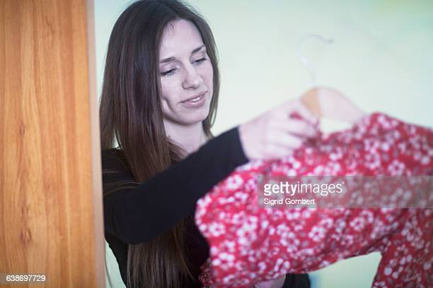 young woman at home, deciding what to wear - pink blouse stock pictures, royalty-free photos & images