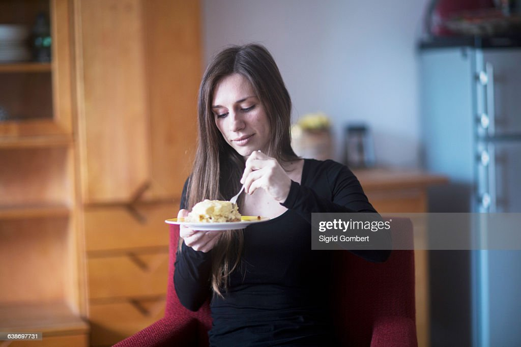 Young woman at home, eating lunch : Stock-Foto