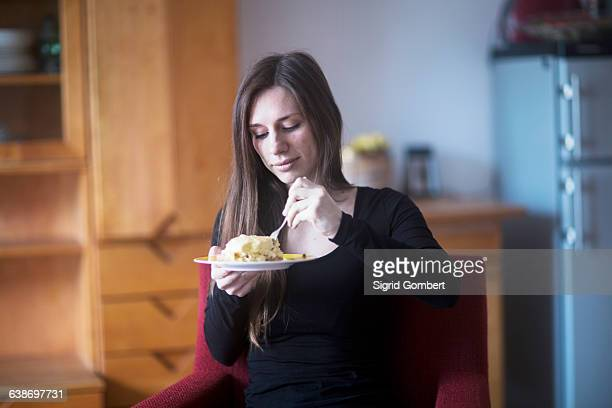 young woman at home, eating lunch - sigrid gombert stockfoto's en -beelden