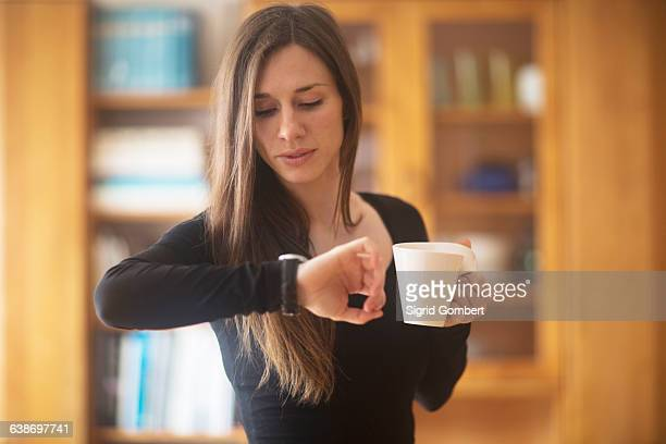 young woman at home, holding hot drink, looking at watch - woman hurry stockfoto's en -beelden