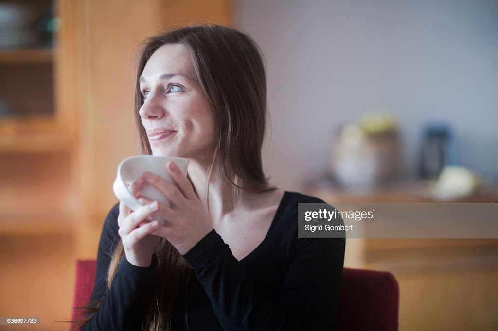 Young woman at home, holding hot drink : Stock-Foto