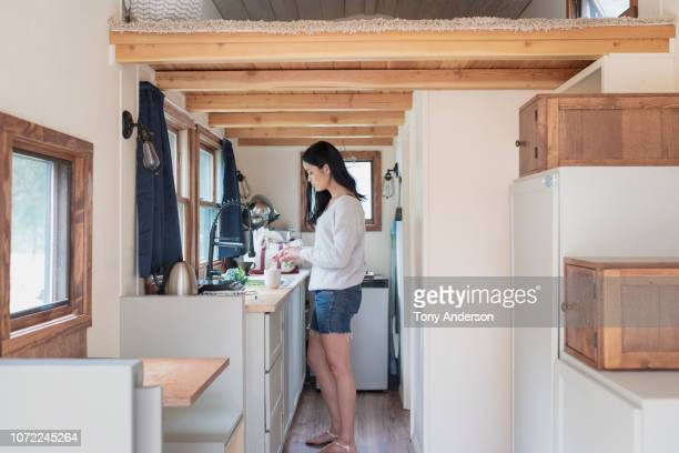 young woman at home in her tiny house - wohngebäude innenansicht stock-fotos und bilder