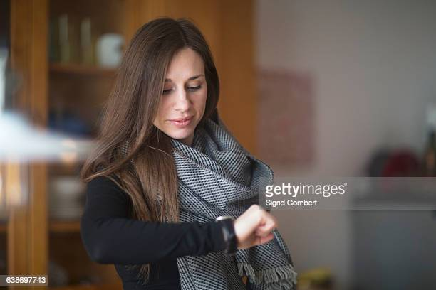 young woman at home, looking at watch - sigrid gombert stock-fotos und bilder
