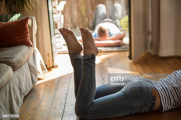 Young woman at home lying barefoot on wooden floor, low section