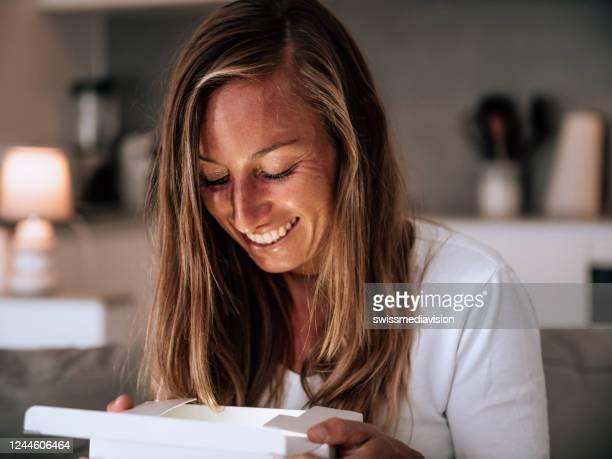 jonge vrouw thuis die giftdoos opent - ontvangen stockfoto's en -beelden
