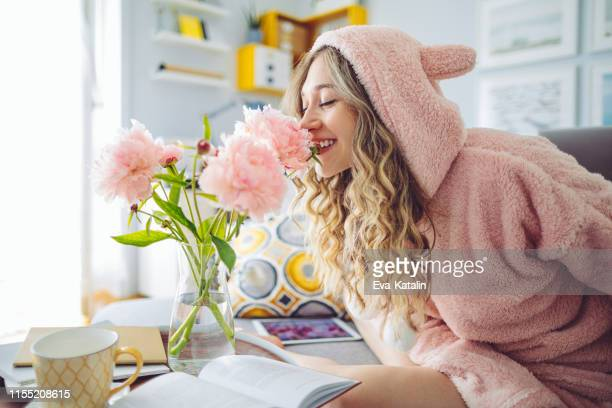 young woman at home - rose colored stock pictures, royalty-free photos & images