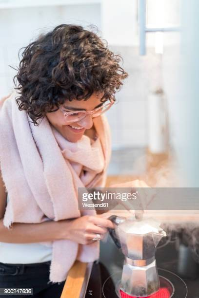 Young woman at home preparing espresso on stove