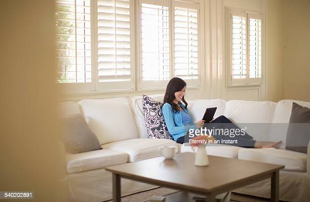 Young woman at home reading her digital tablet
