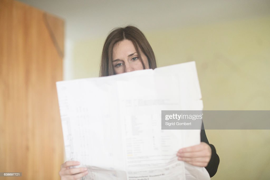 Young woman at home, reading newspaper : Stock-Foto