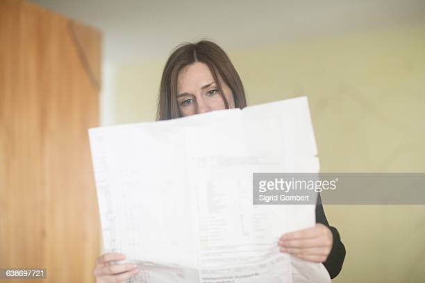 young woman at home, reading newspaper - sigrid gombert stock pictures, royalty-free photos & images