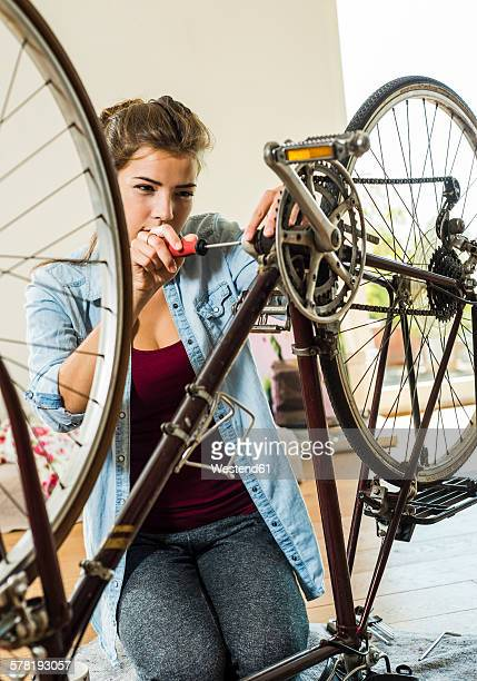 Young woman at home repairing her bicycle