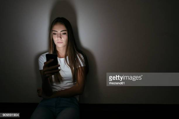 young woman at home sitting on floor using cell phone in the dark - obsessive stock pictures, royalty-free photos & images