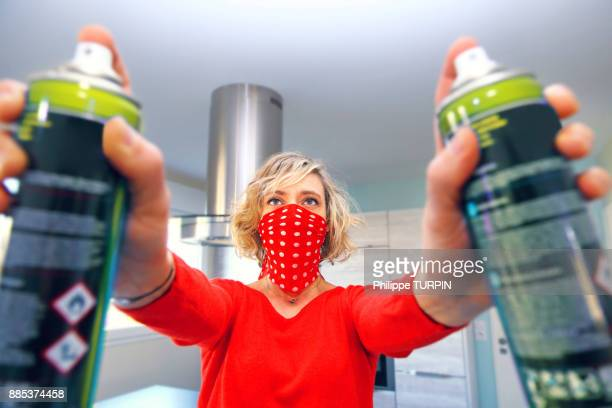 Young woman at home using air spray