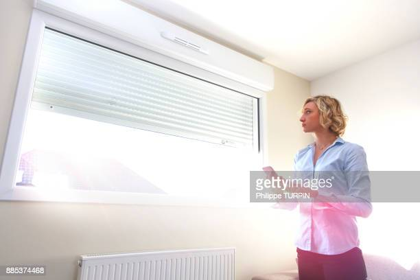 young woman at home using smartphone to open windows - roller shutter stock pictures, royalty-free photos & images