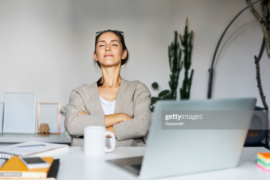 Young woman at home with laptop on desk having a break : Stock Photo
