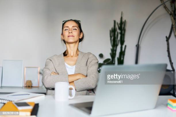young woman at home with laptop on desk having a break - contented emotion stock pictures, royalty-free photos & images