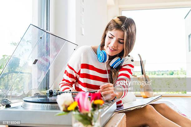 Young woman at home with record player
