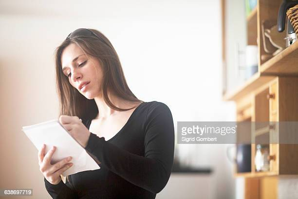 young woman at home, writing on notepad - sigrid gombert stock-fotos und bilder
