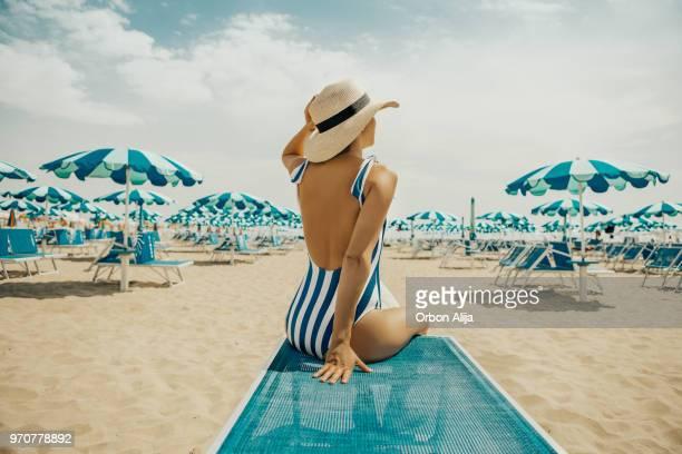 young woman at italian beach - ombrellone da spiaggia foto e immagini stock