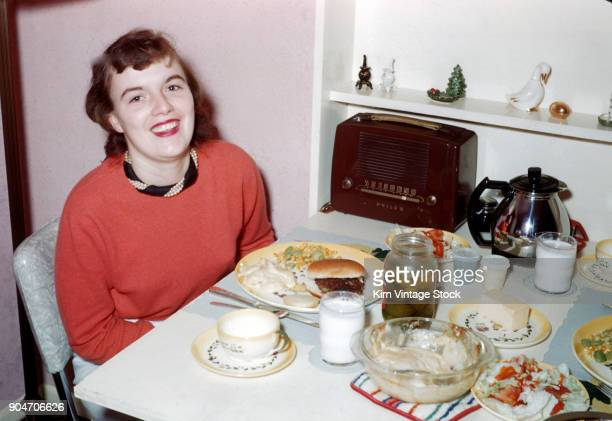 Young woman at kitchen table, ca. 1957.