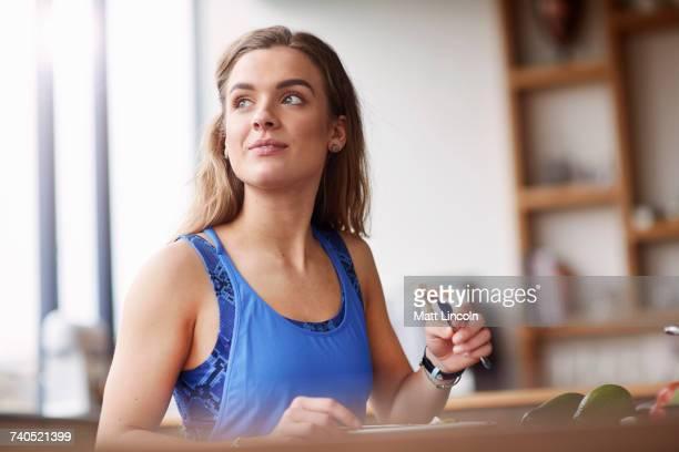 Young woman at kitchen table eating feta salad