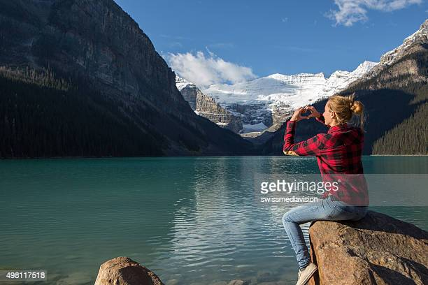 Young woman at lake Louise making heart shape