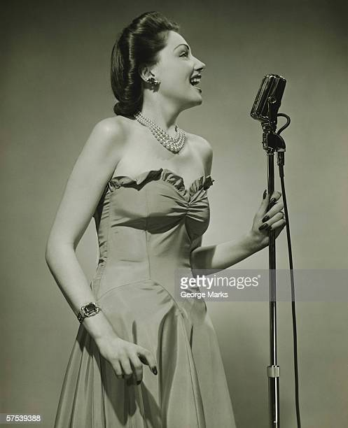 Young woman at microphone, singing, (B&W)