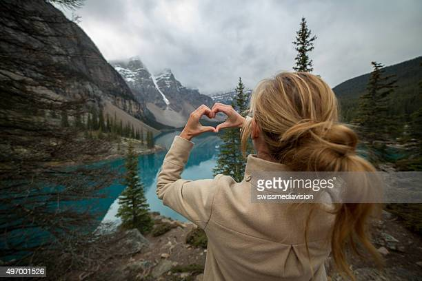 Young woman at Moraine lake makes a heart shape frame