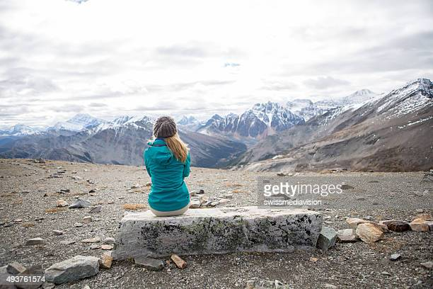 Young woman at mountain top contemplating the landscape