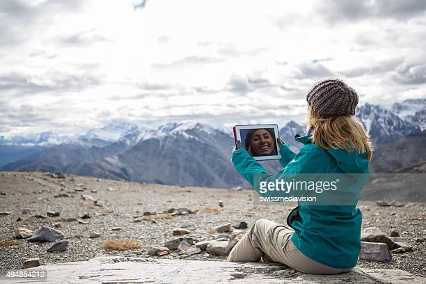 Young woman at mountain top using digital tablet
