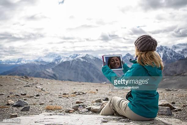 Mujer joven en la cima de la montaña con tableta digital