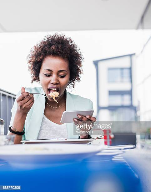 Young woman at outdoor restaurant eating pasta while looking at her smartphone