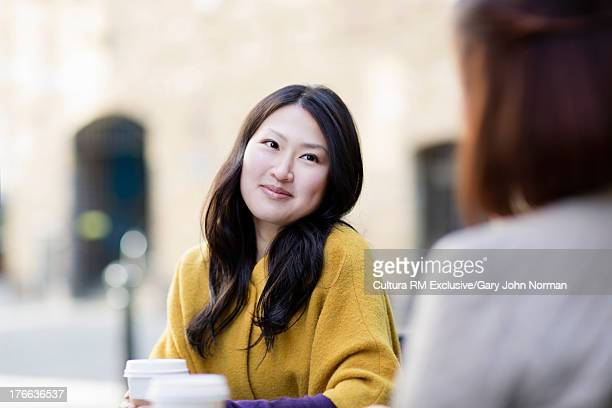 Young woman at pavement cafe, smiling