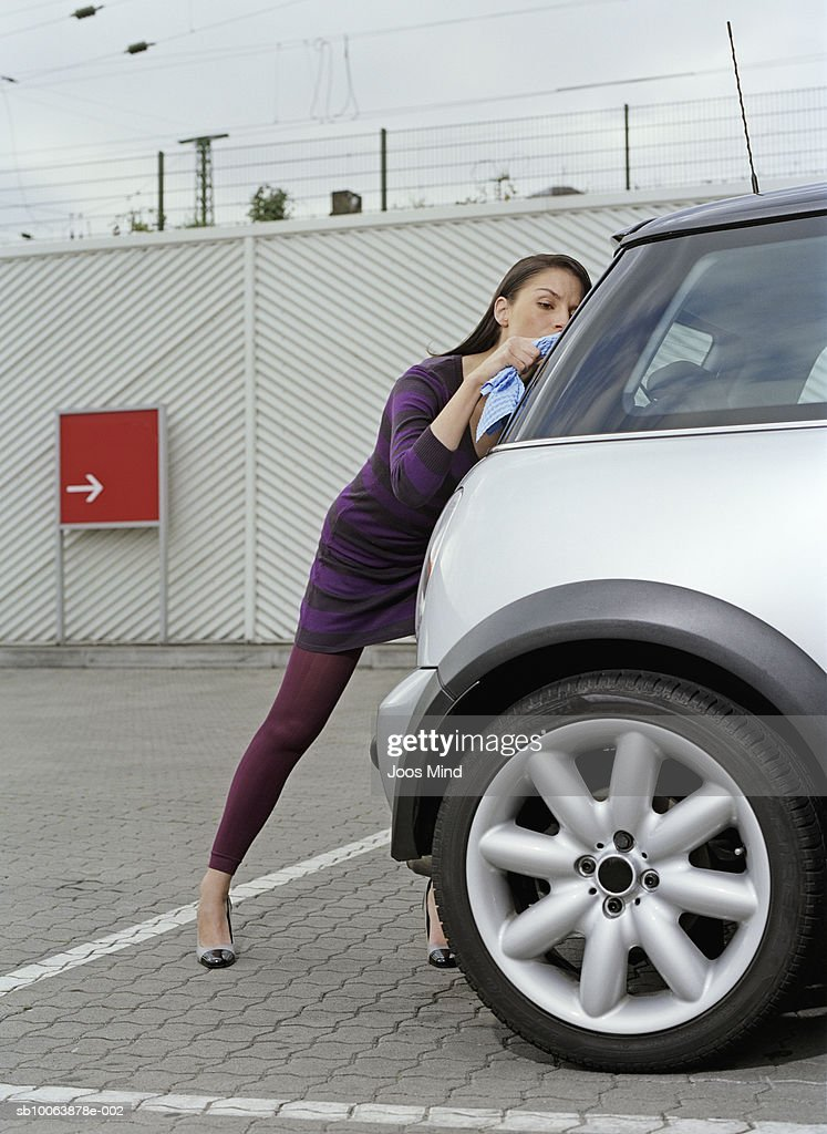 Young woman at petrol station polishing car window : Stock Photo
