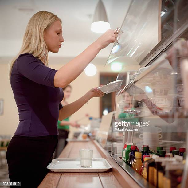 Young woman at self-service counter in canteen
