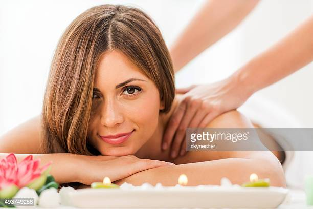 Young woman at spa receiving back massage.
