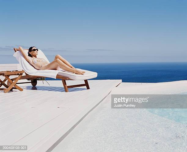 young woman at spa relaxing on sunlounger by outdoor pool - cadeira recostável - fotografias e filmes do acervo