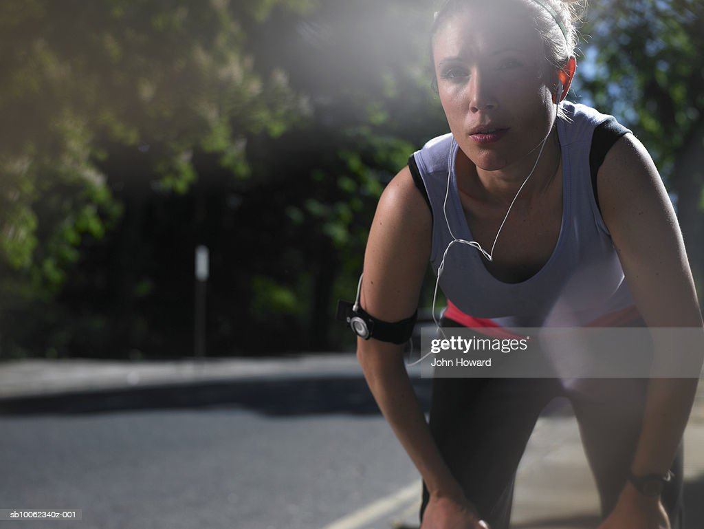 Young woman at street breathing heavily after jogging, lens flare : Stock Photo