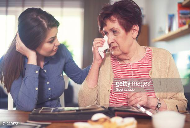 Young woman at table with grandmother crying while looking at photo album