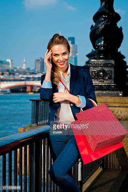 Young woman at Thames River in London, holding shopping bags