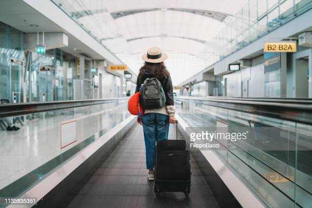 young woman at the airport with a suitcase - arrival stock pictures, royalty-free photos & images