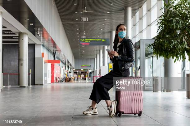 young woman at the airport with luggage, wearing n95 face masks - aeroplane stock pictures, royalty-free photos & images