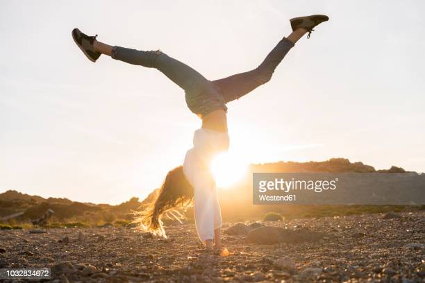 young woman at the beach, doing handstand at sunset - handstand stock pictures, royalty-free photos & images